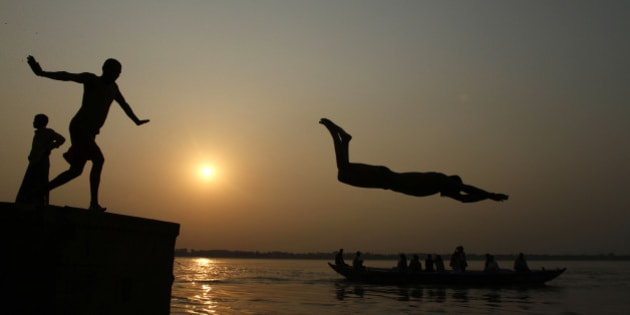 An Indian boy dives into the River Ganges, as tourists ride a boat in Varanasi, India,  Thursday, Sept. 27, 2012.  Varanasi is among the world's oldest cities, and millions of Hindu pilgrims gather annually here for ritual bathing and prayers in the Ganges river considered holiest by Hindus. (AP Photo/Rajesh Kumar Singh)