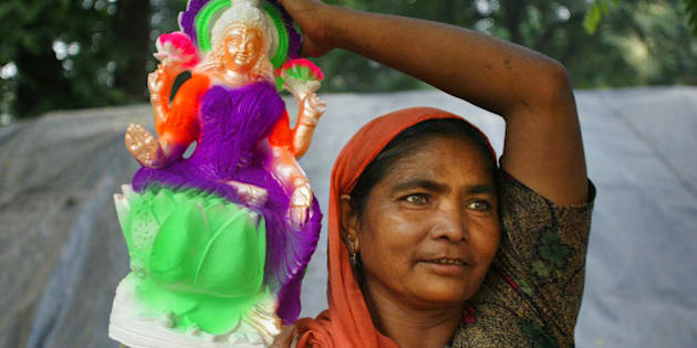 A woman carries an idol of Hindu Goddess Lakshmi for sale in Allahabad, India, Sunday, Oct. 15, 2006. Hindus buy idols of gods and goddesses ahead of Diwali, the festival of lights that is celebrated on Oct.21. (AP Photo/Rajesh Kumar Singh)