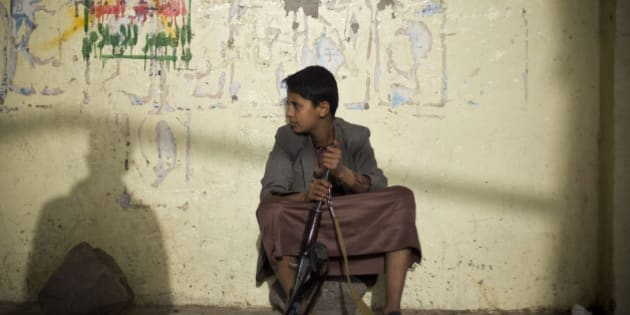A boy holds his weapon, as he sits on guard near the site of a protest against Saudi-led airstrikes in Sanaa, Yemen, Friday, April 10, 2015. Pakistani lawmakers on Friday unanimously voted to stay out of the Saudi-led air coalition targeting Shiite rebels in Yemen in a blow to the alliance, while planes loaded with badly needed medical aid landed in Yemen's embattled capital, Sanaa, in the first such deliveries since the airstrikes started more than two weeks ago. (AP Photo/Hani Mohammed)