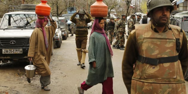 Kashmiri women carry pots filled with drinking water on their heads and walk past security officers standing guard during a gunbattle at Hardshoora village, 35 kilometers (20 miles) north of Srinagar, India, Thursday, April 2, 2015. Suspected Kashmiri rebels and Indian security personnel were engaged in a fierce gunbattle Thursday in the Himalayan territory, officials said. (AP Photo/Mukhtar Khan)