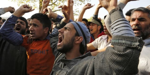 Kashmiri Muslim villagers shout slogans against Indian army during the funeral procession of Khaled Muzaffar, a civilian  in Tral, some 38 Kilometers (24 miles) south of Srinagar, Indian controlled Kashmir, Tuesday, April 14, 2015. Violent protests erupted in the Indian-controlled portion of Kashmir on Tuesday after a civilian and a militant were killed in an encounter with the army, officials in the troubled Himalayan region said. Relatives and angry locals say the civilian was actually tortured to death.(AP Photo/Mukhtar Khan)