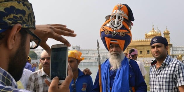 An Indian Sikh devotee (L) takes photographs of a Nihang (Sikh religious warrior) at the Sikh shrine Golden Temple in Amritsar on April 14, 2015. Baisakhi is a festival celebrated in the Punjab region, coinciding with other festivals celebrated on the first day of Vaisakh such as the Tamil and Bengali New Year. AFP PHOTO/NARINDER NANU        (Photo credit should read NARINDER NANU/AFP/Getty Images)