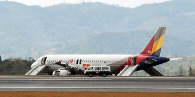 An Asiana Airlines Airbus A320 aircraft is seen with its evacuation slides deployed after it overran a runway at the Hiroshima airport in Mihara in Hirishima prefecture, western Japan on April 15, 2015. More than 20 passengers were injured when an Asiana Airlines Airbus A320 overran a runway at the Hiroshima airport on April 14. The South Korean carrier's Flight OZ162, which took off at Incheon airport, was attempting to land in Hiroshima when the incident occurred.  AFP PHOTO / JIJI PRESS    JAPAN OUT        (Photo credit should read JIJI PRESS/AFP/Getty Images)