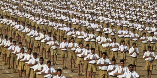 Volunteers of the militant Hindu group Rashtriya Swayamsevak Sangh (RSS) perform Surya Namaskar or sun salutation during the concluding ceremony of its three day long karyakarta shibir, or workers' conclave on the outskirts of Ahmadabad, India, Sunday, Jan. 4, 2015. The RSS, parent organization of the ruling Bharatiya Janata Party, combines religious education with self-defense exercises. The organization has long been accused of stoking religious hatred against Muslims. (AP Photo/Ajit Solanki)