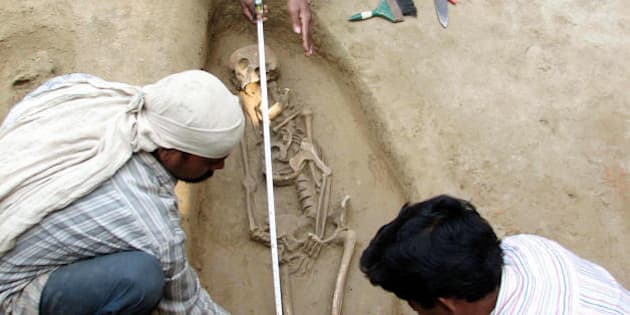 Research workers of India's Vishwa Bharati University measure a human skeleton found at an excavation site in Babupur village, Malda, some 350 Kms. north of Kolkata on February 23, 2008. The researchers working over four years, have allready recovered nine human skeleton form the historical ruins which is expected to be from the Paul and Sen era of 7th century.  AFP PHOTO/STR (Photo credit should read STR/AFP/Getty Images)