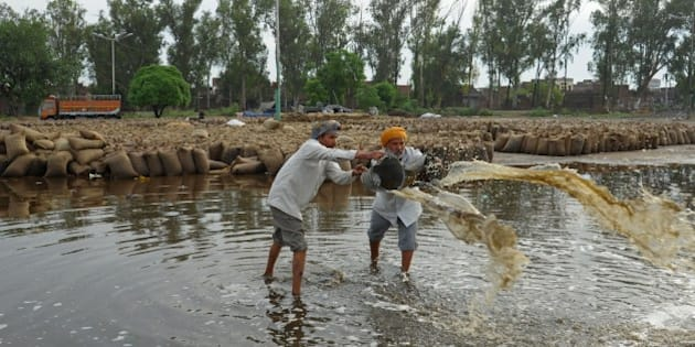 Indian labourers bail accumulated rainwater near flooded sacks of wheat after unseasonal overnight rains soaked the area at a grain distribution point in  Amritsar on May 13, 2014. Punjab is India's largest wheat producing state, contributing nearly 70 percent of the national total. Farmers in Punjab state have incurred huge losses as unseasonal rainfall damaged wheat crops, washing away prospects of a bumper production. AFP PHOTO/NARINDER NANU        (Photo credit should read NARINDER NANU/AFP/Getty Images)