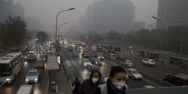 Pedestrians wear masks against the pollution as they cross an overhead bridge over a busy highway in Beijing, China, Saturday, Nov. 29, 2014. The Chinese capital is shrouded by a familiar haze after a respite during the APEC meetings when thousands of factories halted operations and odd-even car plate restrictions brought blue sky weather that the media has nicknamed APEC Blue.  (AP Photo/Ng Han Guan)