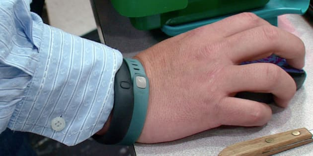 This photo from video taken Oct. 9, 2013 shows the wrist of Tim Davis wearing his FitBit, green, and Nike FuelBand, black, devices he uses to track his physical activity and habits, in New Brighton, Pa. Davis uses several apps and three wearable devices to track his physical activity, vitals and calorie intake. When Davis tipped the scales at 318 pounds two years ago, he bought a Fitbit gadget to track his physical activity and the Lose It! app on his phone to track calories. He bought a Wi-Fi-enabled scale that published his daily weight on his Twitter feed and turned to other apps to track his pulse, blood pressure, daily moods and medications. At one point, Davis said he was using 15 different apps and gadgets, which he said helped him drop 64 pounds by that following year. (AP Photo/Noel Waghorn)