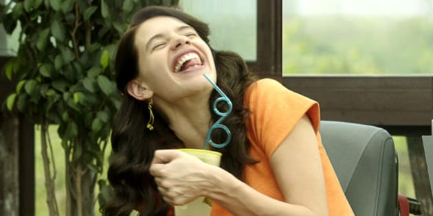 A young woman with wavy black hair is laughing as lowers her head toward a teal straw placed in a yellow glass.
