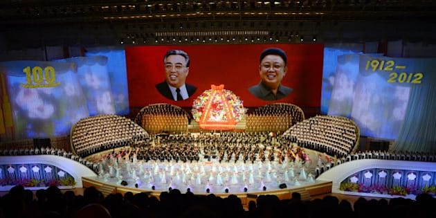 North Koreans performers sing in front of portraits of founding president Kim Il-Sung (L) and his son Kim Jong-Il during celebrations to mark the 100th birth anniversary of the country's founding leader Kim Il-Sung, in Pyongyang on April 16, 2012.  The commemorations came just three days after a satellite launch timed to mark the centenary fizzled out embarrassingly when the rocket apparently exploded within minutes of blastoff and plunged into the sea.   AFP PHOTO / PEDRO UGARTE (Photo credit should read PEDRO UGARTE/AFP/Getty Images)