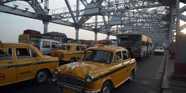 Indian commuters and taxi drivers navigate through heavy traffic on Howrah Bridge in Kolkata on November 7, 2014, where Bollywood actor Amitabh Bachchan is shooting scenes for the film 'Piku'.  Bachchan is shooting scenes in the eastern Indian city for the forthcoming film 'Piku' directed by Sujit Sarkar, with Deepika Padukone and Irrfan Khan also taking part.  AFP PHOTO/Dibyangshu SARKAR        (Photo credit should read DIBYANGSHU SARKAR/AFP/Getty Images)