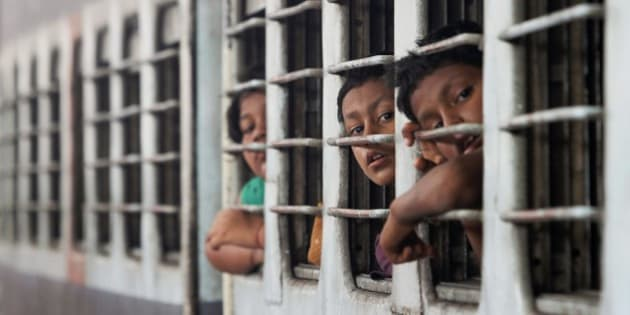 Young passengers peer out of windows of a train at a railway station in Puri, India, Tuesday, July 8, 2014. India's new rail minister Sadananda Gowda on Tuesday proposed allowing foreign investment to modernize the country's cash-strapped state railways. India has one of the world's largest railways, which transports 23 million passengers a day. Indian Railways is one of the world's biggest employers with more than 1.3 million employees. The network lost 300 billion rupees ($5 billion) last year. (AP Photo/Biswaranjan Rout)
