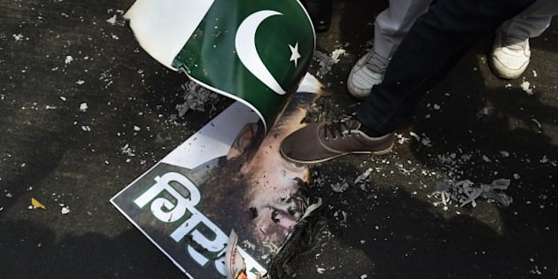 An activist of India's right-wing Shiv Sena steps on a poster of hardline Muslim separatist, Masarat Alam during a protest in New Delhi on April 16, 2015.  Indian police have registered a case against Masarat Alam after  Pakistani flags were raised at a rally in Kashmir.   AFP PHOTO / MONEY SHARMA        (Photo credit should read MONEY SHARMA/AFP/Getty Images)