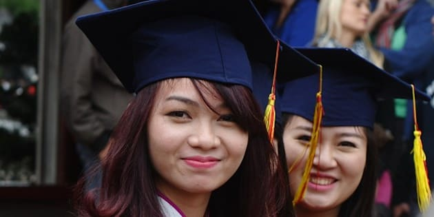 Two students from a local college attend a graduation ceremony at the Temple of Literature in Hanoi on November 18,  2014. The temple is where Vietnam's oldest university was founded in the 11th century under the Ly Dynasty, and is popular with modern-day students who begin to flock in high school, hoping to boost their chances in annual nationwide examinations.    AFP PHOTO / HOANG DINH NAM        (Photo credit should read HOANG DINH NAM/AFP/Getty Images)