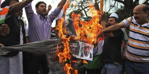 India's Hindu right-wing activists prepare to burn an effigy of an effigy with pictures of Jammu and Kashmir Chief Minister Mufti Mohammed Sayeed. Kashmiri separatist leader Syed Ali Shah Geelani and Masarat Alam during a protest in Jammu, India, Thursday, April 16, 2015. The right-wing activists were protesting after Kashmiri supporters raised pro-Pakistan slogans and waved Pakistani flags at a rally organized by separatists in Indian controlled Kashmir Wednesday. (AP Photo/Channi Anand)