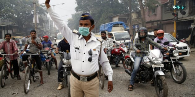 A traffic policeman wears a mask and controls traffic on a busy road in Mumbai, India, Tuesday, April 14, 2015. Air pollution kills millions of people every year, including more than 627,000 in India, according to the World Health Organization. The WHO puts 13 Indian cities in the world's 20 most polluted. (AP Photo/Rajanish Kakade)