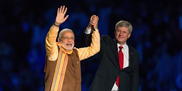 Canadian Prime Minister Stephen Harper (R) and Indian Prime Minister Narendra Modi (L) acknowledge the crowd  during a rally on Prime Minister Modi's first official visit to Canada, April 15, 2015 in Toronto.    AFP PHOTO / GEOFF ROBINS        (Photo credit should read GEOFF ROBINS/AFP/Getty Images)