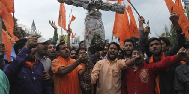 India's Hindu right-wing Shiv Sena activists prepare to burn an effigy of Kashmiri separatist Masarat Alam during a protest in Jammu, India, Thursday, April 16, 2015. The right-wing activists were protesting after Kashmiri supporters raised pro-Pakistan slogans and waved Pakistani flags at a rally organized by separatists in Indian controlled Kashmir Wednesday. (AP Photo/Channi Anand)