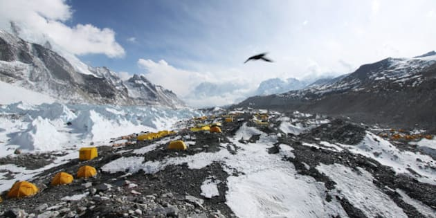 In this Saturday, April 11, 2015 photo, a bird flies over tents set up for climbers at Everest Base Camp in Nepal. More medical staff has been placed at Mount Everest's base camp, and the government has set up a full-time office tent at the camp, with officials providing security, settling disputes among climbers and monitoring the activities of the hundreds of climbers and guides at the camp. Climbers from four teams have already been issued permits allowing them to climb the 8,850-meter (29,035-foot) peak, another 11 written applications are pending and more applications are expected in the next few days, said Gyanendra Shrestha, an official at Nepal's Mountaineering Department. (AP Photo/Tashi Sherpa)