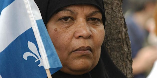 A Pakistani woman holds a Quebec flag during a demonstration called 'No One is Illegal' against the World Trade Organization meeting 27 July 2003 in Montreal.  At the WTO's informal meeting starting 28 July 2003, trade ministers will attempt to find common ground over the divisive issues of farm subsidies and medicine for poorer countries that have stalled the latest round of global trade talks.  AFP PHOTO/Normand BLOUIN  (Photo credit should read NORMAND BLOUIN/AFP/Getty Images)