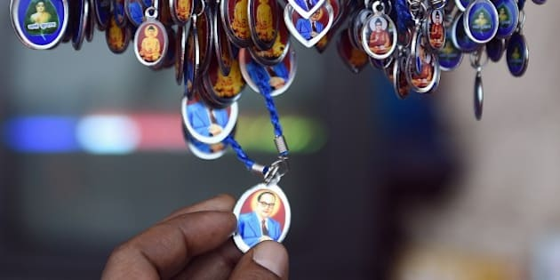 A man inspects a locket with an image of Bhimrao Ambedkar for sale on Ambedkar's 124th birth anniversary near the historic Chaitya Bhoomi memorial in Mumbai on April 14, 2015. Ambedkar known as the messiah of the Dalits and one of the key authors of India's constitution, fought for equal rights for the low-caste during and after British colonial rule, which ended in 1947. Dalits, once known as 'untouchables,' is the term used for those on the lowest rung of India's rigid Hindu caste hierarchy. In recent years things have started to change with the government taking steps to improve the livelihood of the Dalits by improving education and creating job opportunities. AFP PHOTO/ Indranil MUKHERJEE        (Photo credit should read INDRANIL MUKHERJEE/AFP/Getty Images)