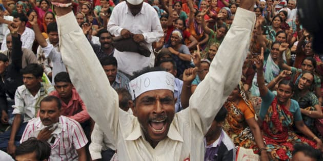 An Indian farmer shouts slogans during a protest rally in Gandhinagar, 30 kilometers (19 miles) north of Ahmadabad, India, Tuesday, June 18, 2013. Protesters mainly farmers railed against the Gujarat government's decision to develop Mandal-Becharaji as Special Investment Region (SIR). (AP Photo/Ajit Solanki)