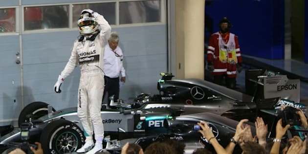 Mercedes AMG Petronas British driver Lewis Hamilton gestures towards members of his team as he celebrates on top of his car after winning the Formula One Bahrain Grand Prix at the Sakhir circuit in the desert south of the Bahraini capital, Manama, on April 19, 2015.  AFP PHOTO / MARWAN NAAMANI        (Photo credit should read MARWAN NAAMANI/AFP/Getty Images)