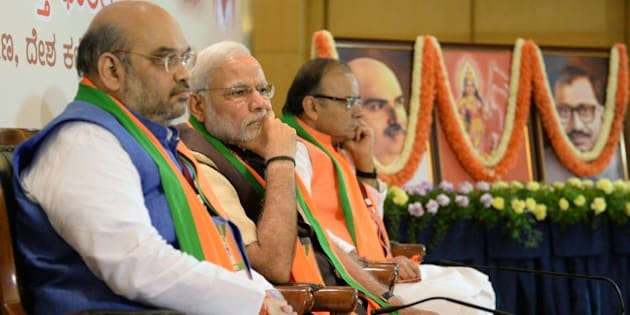 Indian Bharatiya Janata Party (BJP) national president Amit Shah (L), Prime Minister Narendra Modi (C) and Finance Minister Arun Jaitely look on during a BJP office bearers' meeting held on the eve of the party's National Executive committee meeting in Bangalore on April 2, 2015. The two-day National Executive meeting, scheduled to begin on April 3, 2015 in Bangalore, will be the first such meeting since the BJP came to power last year. AFP PHOTO / Manjunath KIRAN        (Photo credit should read MANJUNATH KIRAN/AFP/Getty Images)