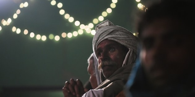 An Indian villager waits near a Hindu temple as a Hindu priest readies himself to run through a huge bonfire in the northern town of Phalem on March 6, 2015.  Hundreds of villagers from the farming town crowded rooftops and a small square as a Hindu priest walked through a raging fire in a ritual that marks the burning of demon Holika on the day of Holi or 'festival of colors'.    AFP PHOTO / Roberto SCHMIDT        (Photo credit should read ROBERTO SCHMIDT/AFP/Getty Images)