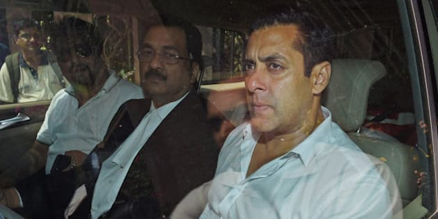 Bollywood actor Salman Khan, right, sits in a car outside a court in Mumbai, India, Friday, March 27, 2015. Khan refuted charges that he was driving the car which had rammed into a bakery shop in Mumbai on Sept. 28, 2002, killing one person and injuring four others who were sleeping on the pavement. (AP Photo/Press Trust of India)
