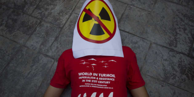 A protestor lies on the ground with an anti-nuclear placard covering his face during a protest in Bangi outside Kuala Lumpur, Malaysia on Tuesday, April 21, 2015. In conjunction with the World Earth Day on April 22, about a dozen protestors from the Malaysia Socialist Party gathered outside the Malaysia Nuclear Agency to protest the development plans of nuclear reactor in Malaysia. (AP Photo/Joshua Paul)