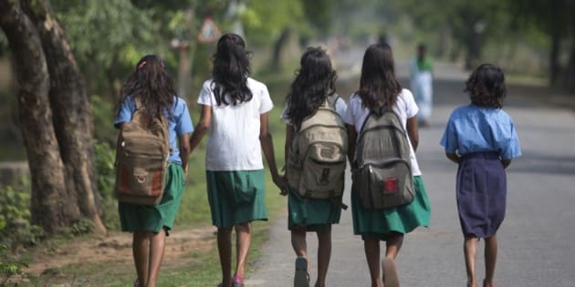 Indian girls walk to a school at Burha Mayong village about 45 kilometers (28 miles) east of Gauhati, India, Thursday, April 9, 2015. According to the UNESCO Education for All Global Monitoring Report 2015, only half of all countries have achieved the most watched goal of universal primary enrollment. The report launched Thursday says, India has reduced its out of school children by over 90% Since 2000. (AP Photo/ Anupam Nath)
