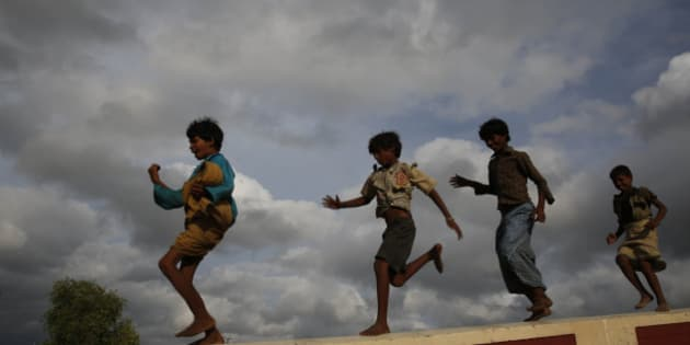 Children play as monsoon clouds hover in the sky, in Allahabad, India, Sunday, July 6, 2014. The monsoon rains which usually hit India from June to September are crucial for farmers whose crops feed hundreds of millions of people.(AP Photo/ Rajesh Kumar Singh)