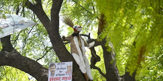 Indian farmer Gajendra Singh stands on a tree before committing suicide during an Aam Aadmi Party rally in New Delhi on April 22, 2015.  A farmer hanged himself in front of hundreds of protesters gathered in the centre of the Indian capital on April 22 to rally against the government's contentious reform of land purchasing laws.  AFP PHOTO/Chandan KHANNA        (Photo credit should read Chandan Khanna/AFP/Getty Images)