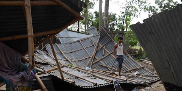 An Indian resident walks on the roof of his shattered home in the village of Gazole, Malda District some 250kms east of Patna on April 22, 2015, after an overnight storm hit many states of eastern India.  A powerful storm swept through India's eastern states including Bihar and West Bengal overnight leaving at least 33 people dead and destroying crops and properties, officials and a report said. The storm lashed several districts across the impoverished state of Bihar, uprooting trees and toppling power lines, the officials said. AFP PHOTO/STR        (Photo credit should read STRDEL/AFP/Getty Images)