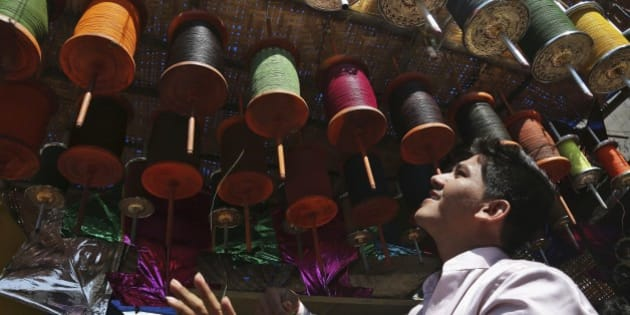 An Indian vendor winds strings for kites as he waits for customers at his shop ahead of the Hindu festival of Makar Sakranti, also knowns as kite festival, in Hyderabad, India, Monday, Jan. 12, 2015. Kites are flown in many parts of India during the Hindu festival of Makar Sakranti to be celebrated on Jan. 14 to mark the transition of winter to spring. (AP Photo/Mahesh Kumar A.)