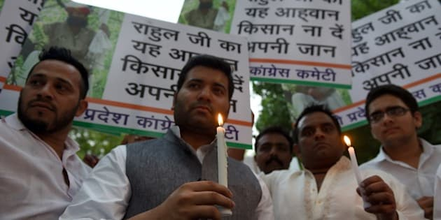 Delhi Congress workers hold candles during a candle light vigil for the suicide of an Indian farmer, in New Delhi on April 23, 2015.   An India farmer hanged himself in front of hundreds of protesters gathered in the centre of the Indian capital on April 22, 2015, to rally against the government's contentious reform of land purchasing laws.  AFP PHOTO/MONEY SHARMA        (Photo credit should read MONEY SHARMA/AFP/Getty Images)