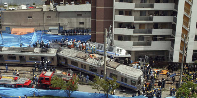 AMAGASAKI, JAPAN - APRIL 25: Rescue workers attempt to free trapped passengers from a crushed commuter train after it derailed and plowed into an apartment building on April 25, 2005 in Amagasaki, Hyogo prefecture, Japan. 49 people have so far been confirmed as dead. (Photo by Getty Images)