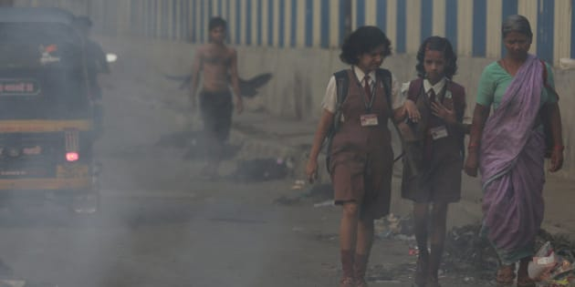 Schoolgirls walk past a burning garbage dump in Mumbai, India, Thursday, April 9, 2015. Air pollution kills millions of people every year, including more than 627,000 in India, according to the World Health Organization. The WHO puts 13 Indian cities in the world's 20 most polluted. (AP Photo/Rafiq Maqbool)
