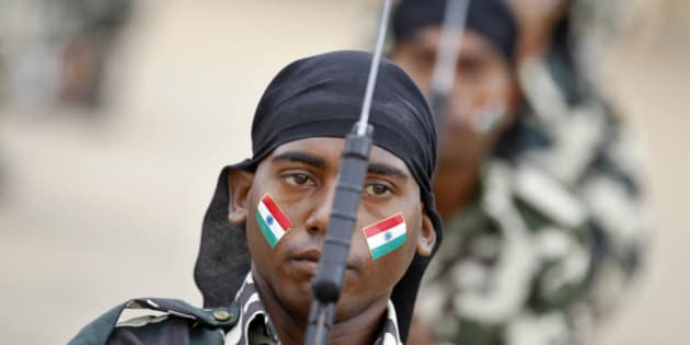 An Indian Central Reserve Police Force (CRPF) personnel with national flag painted on his face participates in arms drill during the passing out parade ceremony of 945 recruits in Bangalore, India, Tuesday, July 9, 2013. CRPF is one of the largest paramilitary force in the world with a strength of over 250,000 personnel, meant to maintain law and order and contain insurgency across India and are also deployed for United Nations missions. (AP Photo/Aijaz Rahi)