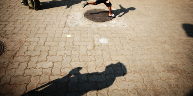 MUMBAI (BOMBAY), INDIA - DECEMBER 03: (ISRAEL OUT) A policeman's silhouette is cast on the ground as a child plays outside the Jewish appartment block, Nariman House, on December, 03, 2008 in Mumbai, India. Two bombs were discovered and defused earlier today by Mumbai police at a train station, the Chhatrapati Shivaji Terminus, which was one of the locations attacked by the terrorists. The attacks left almost 200 hundred dead and injured over 300 people. (Photo by Uriel Sinai/Getty Images)