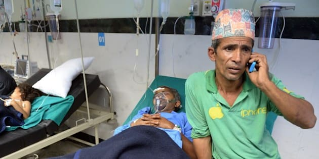 A Nepalese resident talks on the phone as his relative Megh Nath (2R), is treated for injuries sustained in an earthquake at a city hospital in Kathmandu on April 26, 2015. International aid groups and governments intensified efforts to get rescuers and supplies into earthquake-hit Nepal on April 26, 2015, but severed communications and landslides in the Himalayan nation posed formidable challenges to the relief effort. As the death toll surpassed 2,000, the US together with several European and Asian nations sent emergency crews to reinforce those scrambling to find survivors in the devastated capital Kathmandu and in rural areas cut off by blocked roads and patchy phone networks. AFP PHOTO / PRAKASH SINGH        (Photo credit should read PRAKASH SINGH/AFP/Getty Images)