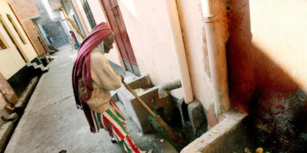 New Delhi, INDIA: In this photo taken, 15 January 2007, Chandrawati, sweeper and drain cleaner by profession, cleans out a drain in the Shahdara area of eastern New Delhi.  In 1993, the government banned the practice, known as 'manual scavenging' which existed for centuries before flush toilets were introduced. Under the law, the construction of dry toilets is banned and existing ones are supposed to be demolished. The law also provides for retraining of people doing the job, 04 February 2007. The national government set 2007 as a deadline to eradicate the practice, but officials admitted privately it would take at least three more years to find new employment for the workers.  AFP PHOTO/Prakash SINGH (Photo credit should read PRAKASH SINGH/AFP/Getty Images)