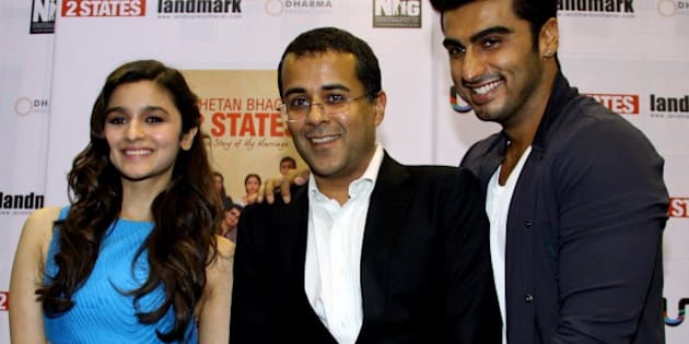 Indian author Chetan Bhagat (C) poses with Indian Bollywood actors Alia Bhatt (L) and Arjun Kapoor (R) during the launch of Bhagat's new book '2 States' in Mumbai on April 7, 2014. AFP PHOTO/STR         (Photo credit should read STRDEL/AFP/Getty Images)