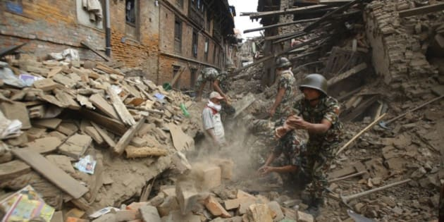 Rescue workers remove debris as they search for victims of earthquake in Bhaktapur near Kathmandu, Nepal, Sunday, April 26, 2015. A strong magnitude 7.8 earthquake shook Nepal's capital and the densely populated Kathmandu Valley before noon Saturday, causing extensive damage with toppled walls and collapsed buildings, officials said. (AP Photo/Niranjan Shrestha)