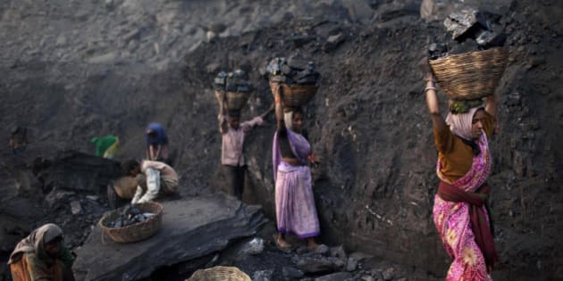 FILE - In this Jan. 7, 2011 file photo, people carry baskets of coal scavenged illegally at an open-cast mine in the village of Bokapahari in the eastern Indian state of Jharkhand where a community of coal scavengers live and work. India's national auditor said Friday, Aug. 17, 2012, the government lost huge sums of money by selling coal fields to private companies without competitive bidding, adding to massive losses from dubious auctions of other state assets. The Comptroller and Auditor General's report to Parliament estimated that private companies got a windfall profit of $34 billion because of the low prices they paid for the fields.(AP Photo/Kevin Frayer, File)