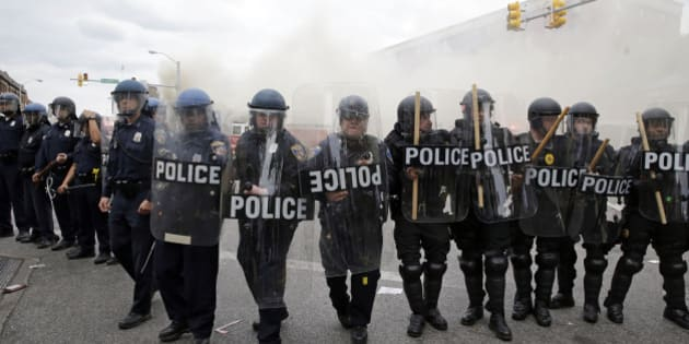 Police advance toward protestors as a store burns, Monday, April 27, 2015, during unrest following the funeral of Freddie Gray in Baltimore. Gray died from spinal injuries about a week after he was arrested and transported in a Baltimore Police Department van. (AP Photo/Patrick Semansky)