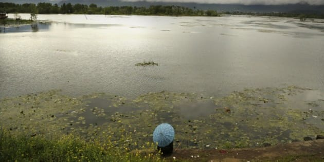 A Kashmiri man holds an umbrella as he fishes sitting on the banks of the Nigeen Lake on a rainy day in Srinagar, Indian controlled Kashmir, Monday, April 27, 2015. (AP Photo/Mukhtar Khan)