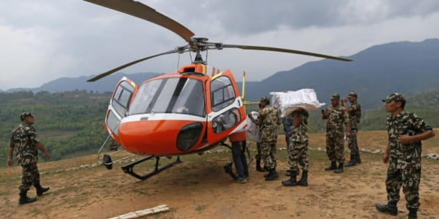 Nepalese soldiers load a helicopter with emergency supplies at a landing zone in the town of Gorkha, Nepal, Tuesday, April 28, 2015. Helicopters crisscrossed the skies above the high mountains of Gorkha district on Tuesday near the epicenter of the weekend earthquake, ferrying the injured to clinics, and taking emergency supplies back to remote villages devastated by the disaster. (AP Photo/Wally Santana)