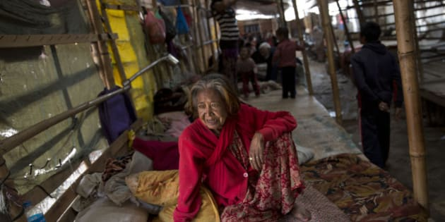An elderly woman watches as she sits inside a residents makeshift area in Bhaktapur, Nepal, Tuesday, April 28, 2015. Many people have camped outdoors in the chilly night cold since Saturday's massive earthquake that shook Nepal's capital and the densely populated Kathmandu valley. (AP Photo/Bernat Armangue)